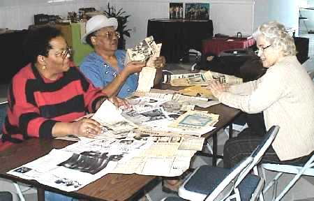 Ladies going over the newspaper clippings